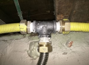 Three pieces of CSST come together at one traditional T-joint, where we split off a branch to feed the existing water heater.